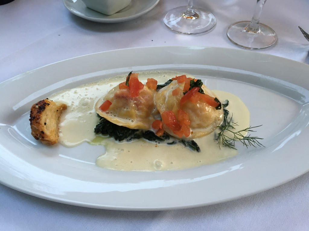 Freshmade ravioli with Atlantic lobster and scallops filling on a bed of spinach with tomatoes and basil.